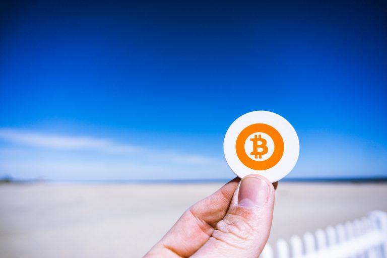 Bitcoin Kurs Prognose mann hält btc münze